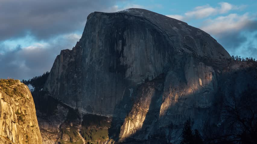 Light rays pierce through the clouds to reveal Half Dome at sunset in Yosemite National Park, California.