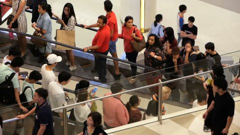 BANGKOK, THAILAND - 26 DECEMBER, 2017: Siam Paragon asian shopping mall interior. Crowds of people on escalators of trade centre. Stress from overpopulation. Yound people go to shop.