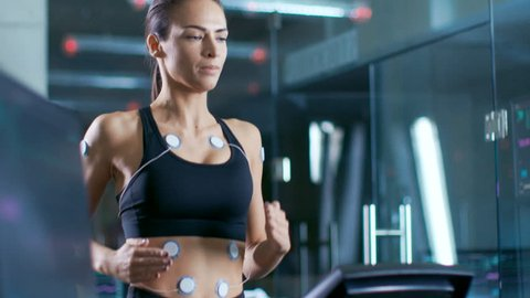 In Scientific Sports Laboratory Beautiful Woman Athlete Runs on a Treadmill with Electrodes Attached to Her Body, Monitors Show EKG Data on Display. Slow Motion.  Shot on RED EPIC-W 8K Helium Camera.
