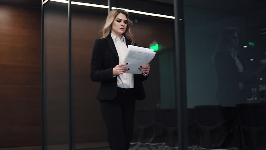 business woman walks down the corridor against the background of the glass partitions of the offices. woman in a business suit at the office