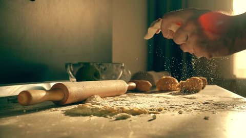 Male cook throwing homemade pasta dough on the table, super slow motion shot