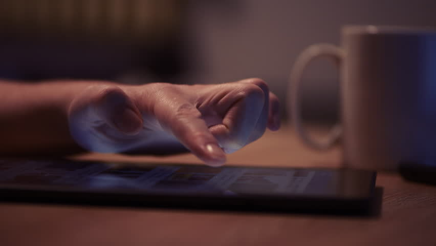 Woman reading online news on digital tablet, close up of hands using device | Shutterstock HD Video #1007635111