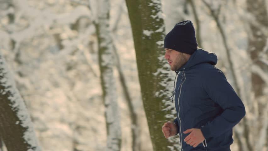 Sportsman Running Through Snowy Winter wood #1007640619