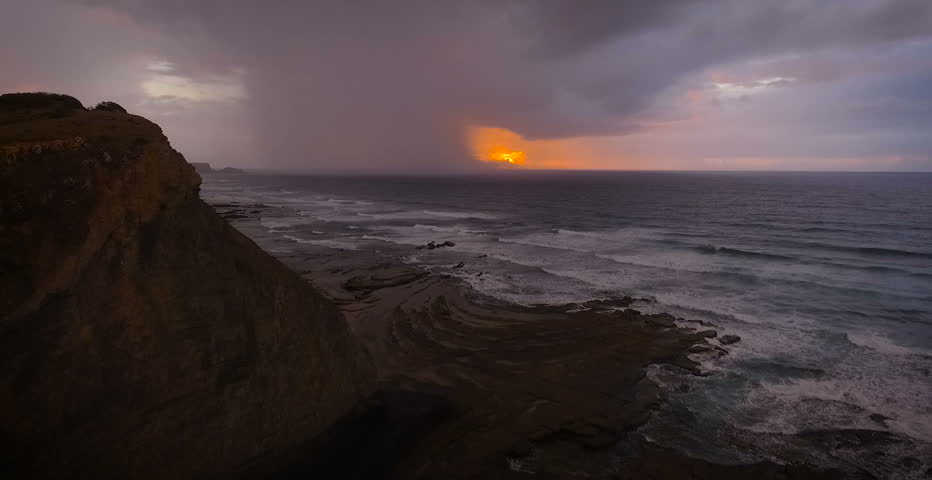 Drone shot of epic sunset with dark storm going across the sea. Algarve, Portugal