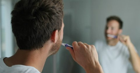 Man brushing his teeth getting ready in the morning doing hygiene routine looking in mirror of home bathroom using toothbrush in for clean dental oral care.