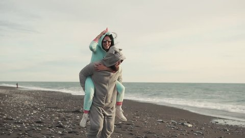 SOCHI, RUSSIA - JANUARY 31, 2018: a loving couple running around the beach on a sunny day, a man and a woman dressed in kigurumi suits, a smiling husband carrying on his back his happy wife