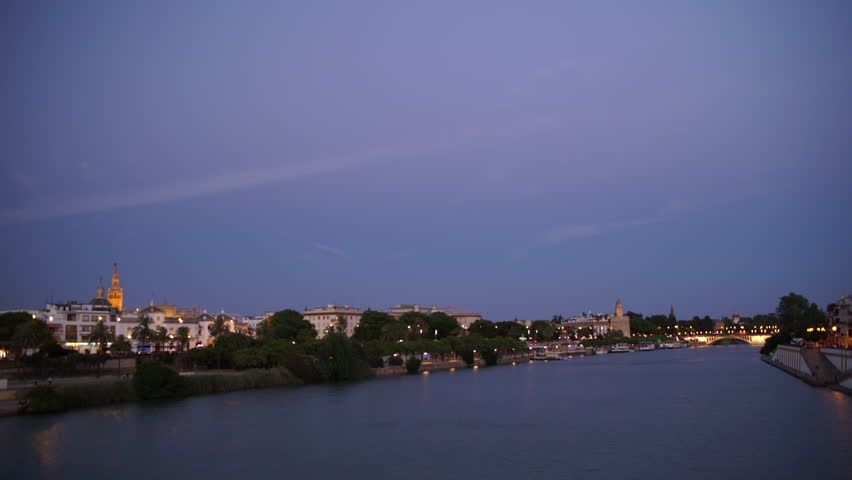 Night shot of Seville city skyline along Guadalquivir River at late evening, Seville, Andalusia, Spain.
