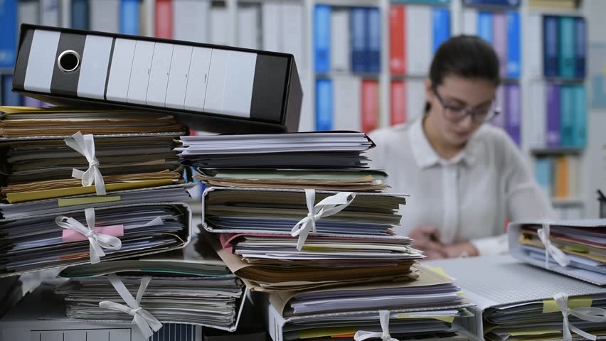 Young woman working in the office and writing documents, she has stacks of paperwork on her desk: work overload concept | Shutterstock HD Video #1007686339