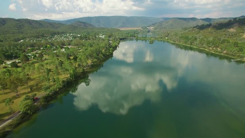 Forward flight over river and beautiful countryside with clouds reflecting in still water