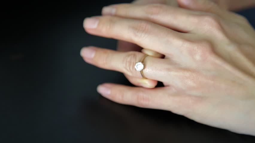 Remove engagement wedding ring from ring finger. Concept of divorce, marriage problem.
