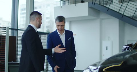 Elegant salesman inviting potential buyer to get in the car in showroom. Slow motion. Shot on Red cinema camera.