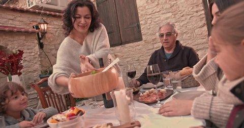 Grandmother serving homemade pasta for family dinner in mediterranean village in Italy