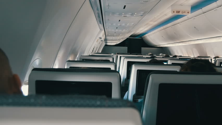 Passengers in comfortable seats of aircraft with the screens in chairs   Shutterstock HD Video #1007712760