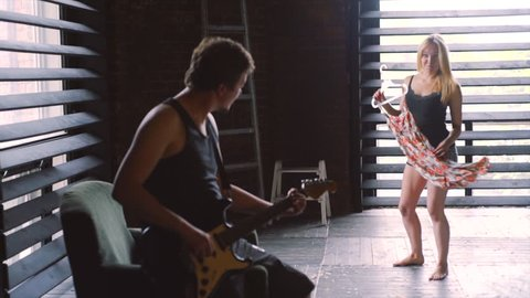 morning in rock-n-roll style,man playing on guitar and girl try on dress and whirling at background  slow motion shot