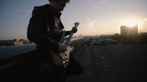 men in rock n roll style standing on the roof and playing on guitar at citiscape background