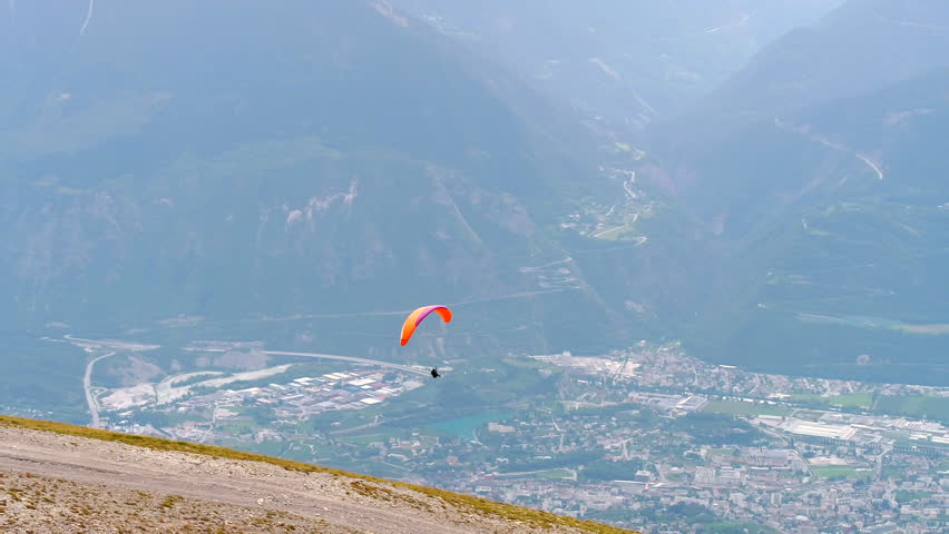 Paragliding in the swiss alps drone aerial shot.  cruising around crans-montana switzerland on a cool summer afternoon.  Shot with the DJI Inspire 2.     Shutterstock HD Video #1007723122