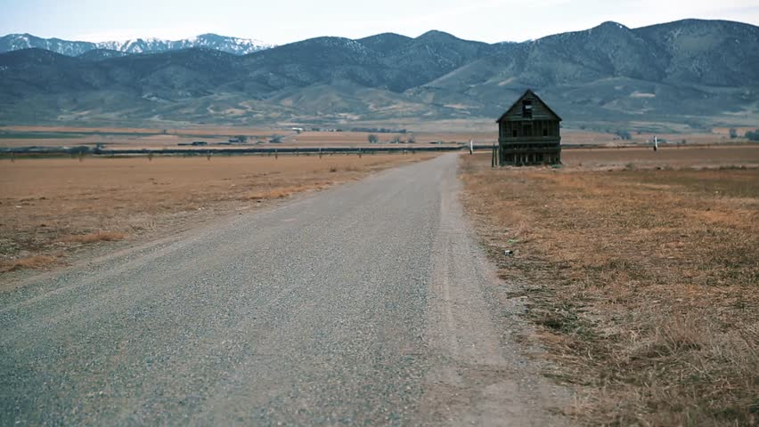 Tumbleweed along the road of a ghost town, abandoned house in background