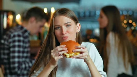 Young happy woman eating tasty fast food burger in cafe