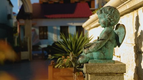 Small angel cupid boy fountain pouring water on sunny day in Batumi, love design