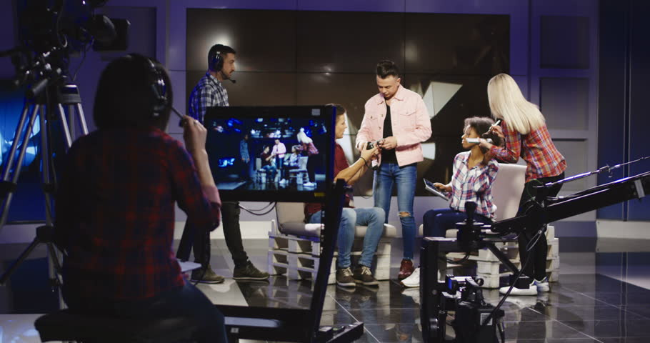 Crew in a production studio getting people ready to participate in an on stage discussion or interview with cameras in the foreground waiting to shoot | Shutterstock HD Video #1007749849