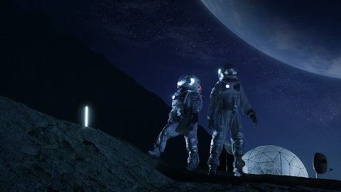 Two Astronauts in Space Suits Stand on the Moon Looking at the Beautiful Earth. In the Background Lunar Base with Geodesic Dome. Moon Colonization and Space Travel Concept. Shot on RED EPIC-W 8K.