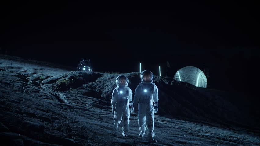 Two Astronauts in Space Suits Walk on the Alien Planet Looking at the Sky. In the Background Base with Geodesic Dome. Other Worlds Colonization and Space Travel Concept. Shot on RED EPIC-W 8K Camera. | Shutterstock HD Video #1007757079