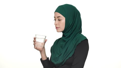 Portrait of beautiful arabic woman in hijab drinking still filtered water from glass being thirsty, over white background. Concept of emotions