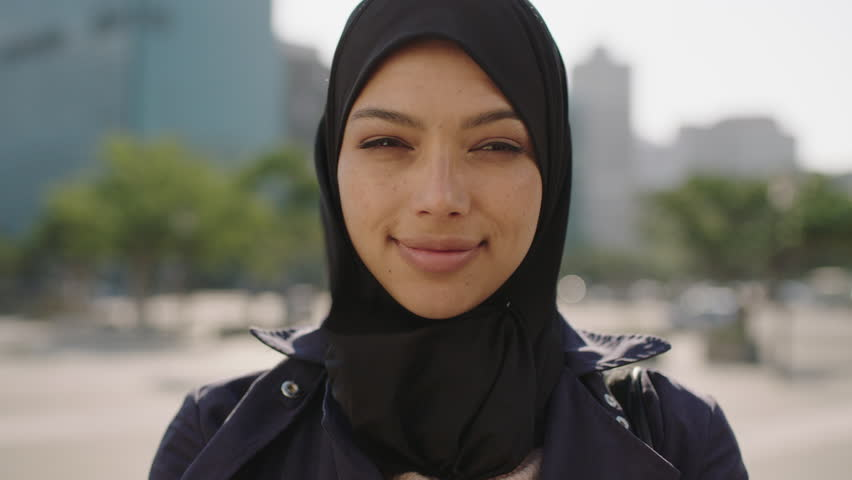 close up portrait of young beautiful muslim business woman wearing hijab headscarf laughing cheerful in city