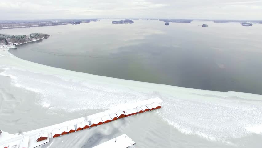 Freezing calm lake landscape with row of red boathouses in Kerimaki, Finland. Aerial shot with slow tilt motion.