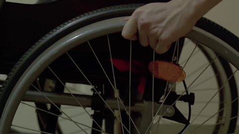 Young guy, a disabled person with a lesion of the spinal cord and legs, multiple sclerosis, moves through the hospital corridor in a wheelchair. Close up.