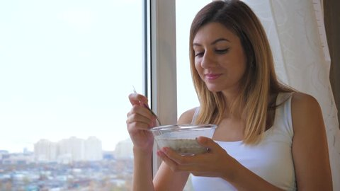 A young pretty brunette woman eats cereal with milk from a bowl. Standing at the window and looks outside. Healthy lifestyle and nutrition. Good mood and pleasure. White linen, 4k, 3840x2160.