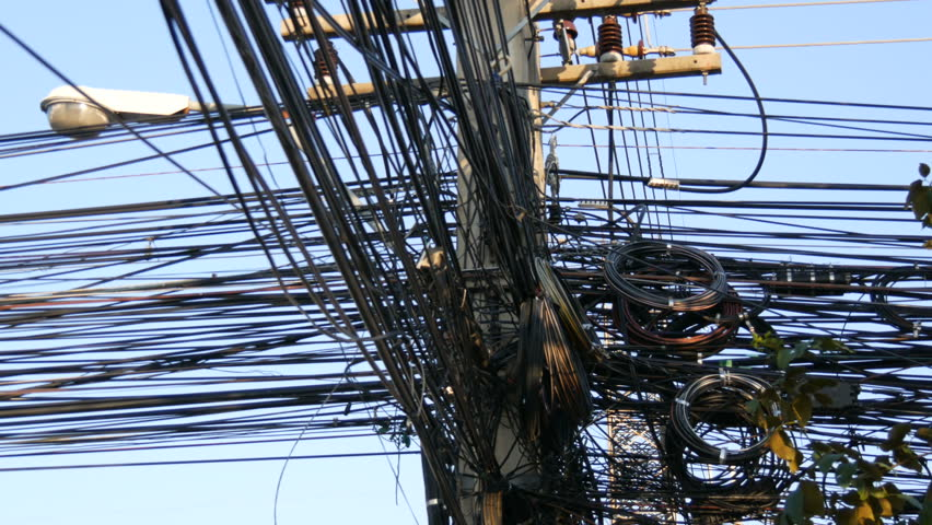Tangled bundles of overhead wires. Electricity system on the streets of Pattaya, Thailand. Tangle of wires on overloaded utilities pole in Thailand wire level pan