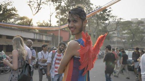A transgender wearing angel wings posing, as sun flares into the camera during LGBT or Gay Pride parade, Mumbai, India (2018)