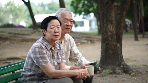 Asian Senior couple drinking morning coffee and tea in park Filename: senior coffee park