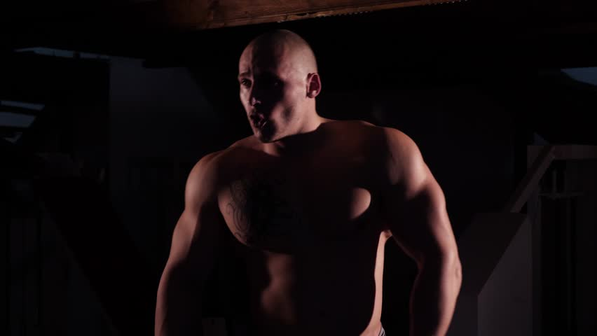 Muscular and topless young bodybuilder fitness male model posing and flexing over black background.  Man posing on a black background, shows his muscles.