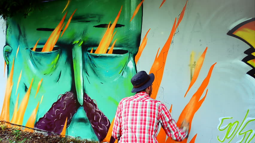 The artist draws graffiti on a fence.