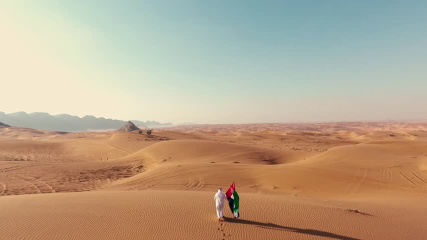 Proud arabian Emirati man holding a UAE flag, walking in the desert