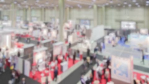 Panoramic view of people visiting a trade show. Background with an intentional blur effect applied.