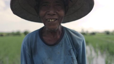 UBUD, BALI INDONESIA / AUGUST 28, 2017 BalInese farmer working on the rice fields smiling at the camera in Bali Indonesia