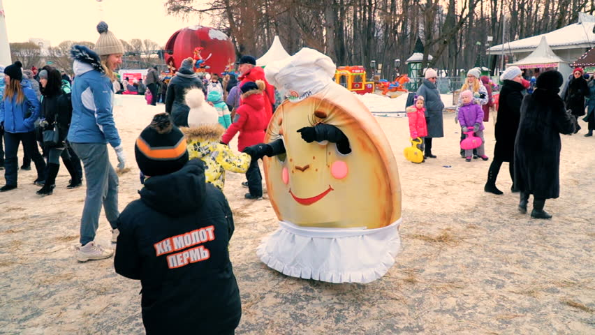Animators in carnival costumes entertain children and their parents. City park, winter. Maslenitsa celebration. Perm, Russia, Fabruary, 18, 2018.