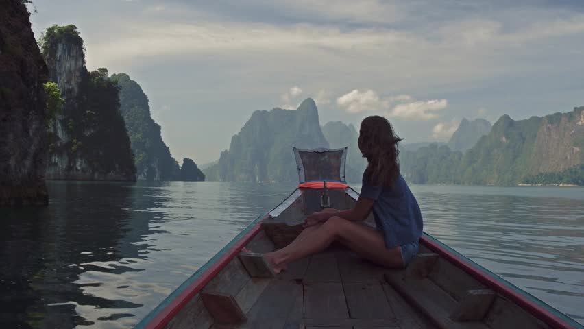 Lifestyle video of pretty travel woman sitting in wood long tail boat on tropical limestone cliffs . Explore and vacation concept. Khao Sok lake, Thailand. | Shutterstock HD Video #1007907979