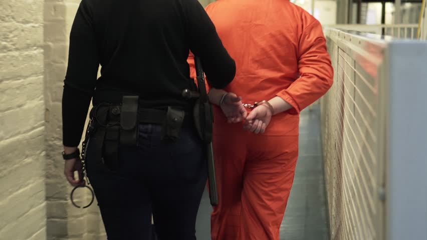Prisoner In Shackles And Handcuffs Walking With Prison Guard, 4K Incarceration.