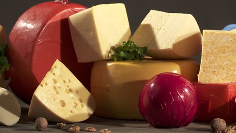 Cheese varieties. Different types of cheeses on wooden table. Stack of cheese wheels, balls and wedges on a dark background. Dolly shot