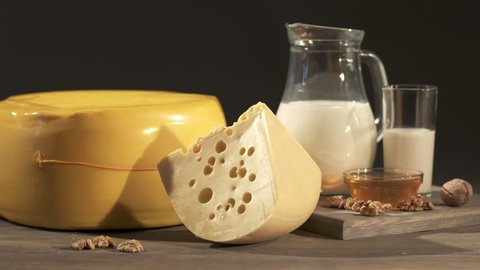 Yellow cheese wheel with wedge of Swiss cheese on an old wooden table. Close-up of board with cheese, milk jug, nuts and honey on a dark background. Dolly shot