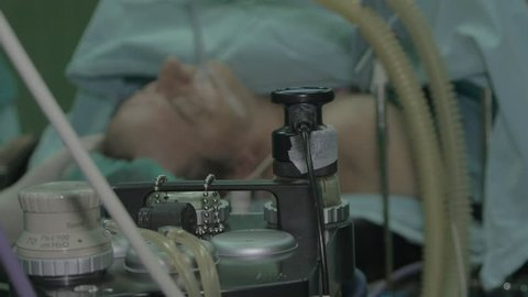 Surgical equipment, surgery oxygen machine in focus, male mature patient under anesthesia with mask and tube on face lying on the table in the blurred background, procedure in operating room, close up