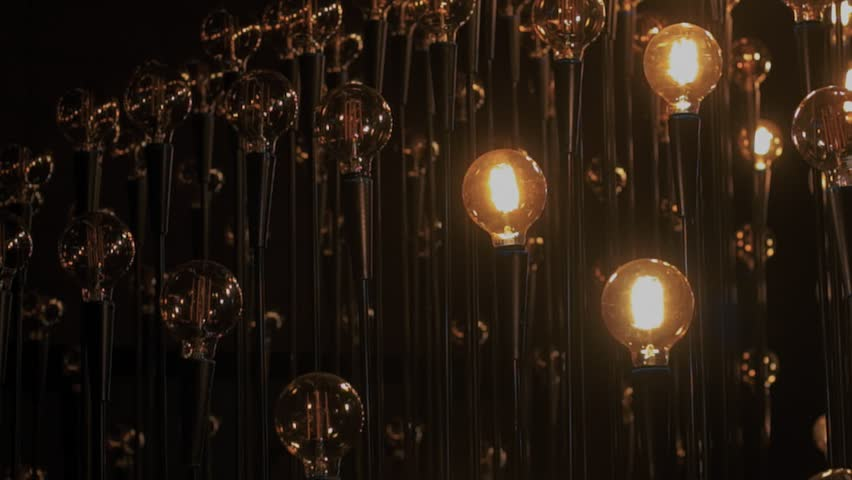 Close up on multitude of retro vintage light bulbs beam and glimmer in darkness with warm tungsteen light, edison trendy ligh source as concept of new idea, realization or discovery | Shutterstock HD Video #1007936959