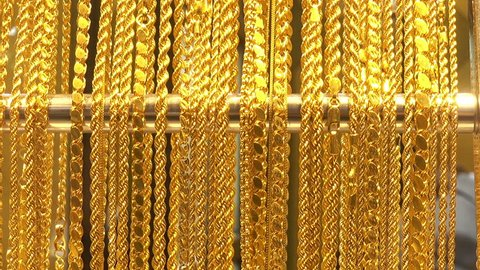 A lot of different gold chains in the shop window of the jewelry store. HD video clip