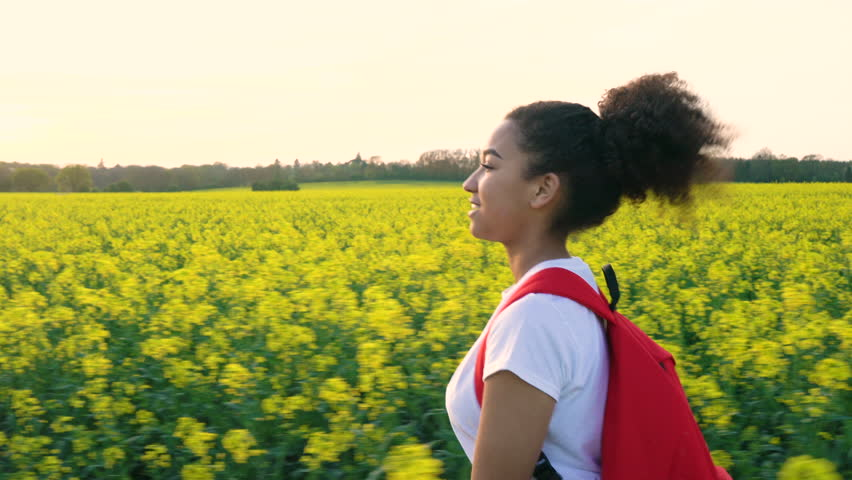 4K tracking video clip of beautiful happy mixed race African American girl teenager female young woman hiking with red backpack in field of rape seed yellow flowers
