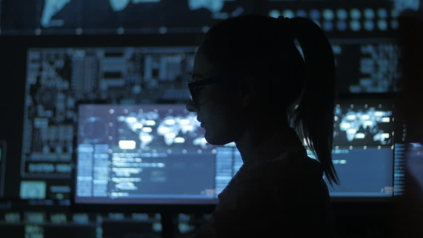 Silhouette of young woman IT programmer working at a computer in the data center filled with display screens | Shutterstock HD Video #1007954359
