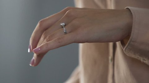 Stressed lady with shaking hands taking off ring, divorce, relations break up